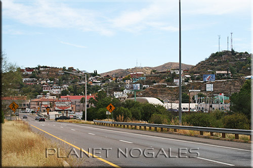 Entering Nogales on I-19 from the North, most of the border parking lots are at or near where the road curves to enter downtown Nogales, Arizona. To the right are the hills of Nogales, Sonora