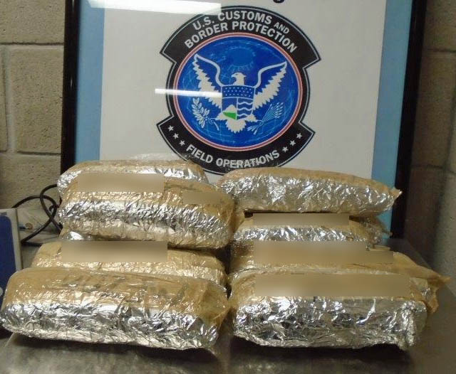 Bundles of heroin, coke and pot discovered in the undercarriage of a Cadillac Dec 2016